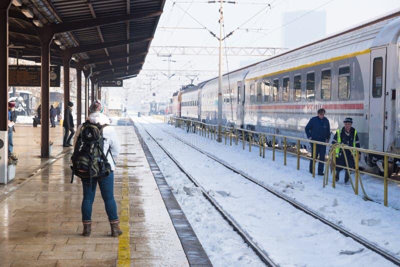 Zagreb, Croatia: January 7 2016: Girl waiting at the platform of the trainstation Zagreb along snowed trainrails royalty free stock image