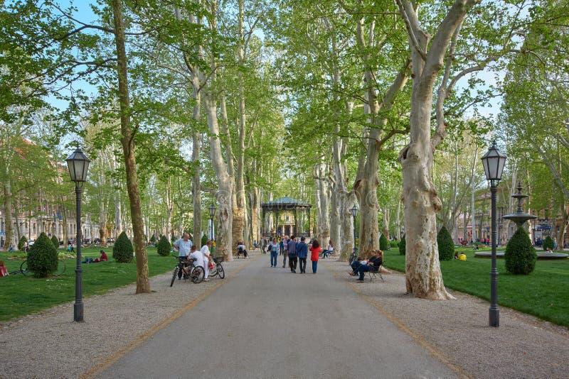Zagreb, Croatie, le 24 avril 2019 : Promenade verte avec vue sur le vieux pavillon de cru en parc de Zrinjevac photos libres de droits