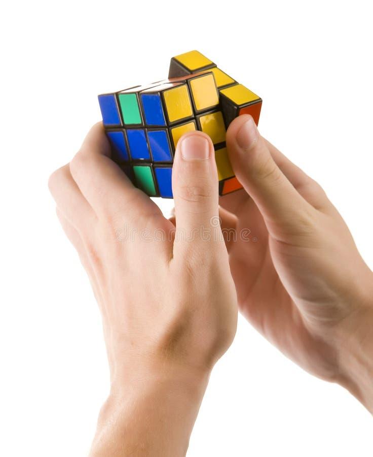 ZAGREB KROATIEN - MARS 13, 2015: Händer som löser den Rubiks kuben Den Rubiks kuben uppfinns av Erno Rubik i 1974 Han är en ungra arkivbild