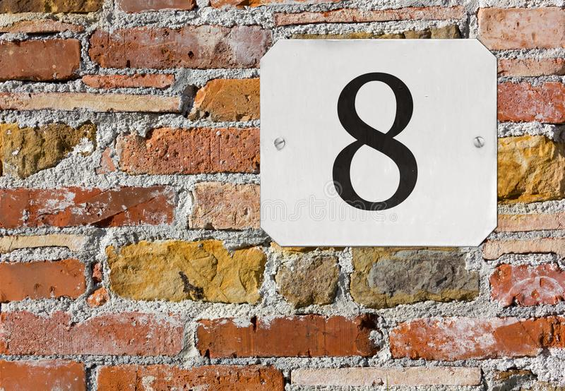 Zahl 8 Hausnummer auf einer Backsteinmauer lizenzfreie stockfotos