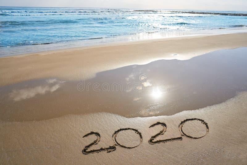 Zahlen des Jahres 2020 buchstabieren geschrieben auf Strand stockbilder