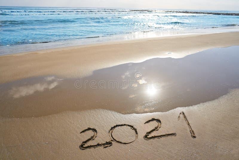 Zahlen des Jahres 2021 buchstabieren geschrieben auf Strand stockfotos