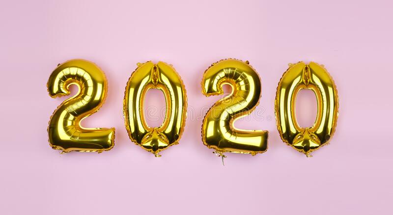 2020 Zahlen: Goldfolienballons auf rosafarbenem Hintergrund Neujahrspartygestaltung Metallische Luftballons für Silvesterabend lizenzfreie stockbilder