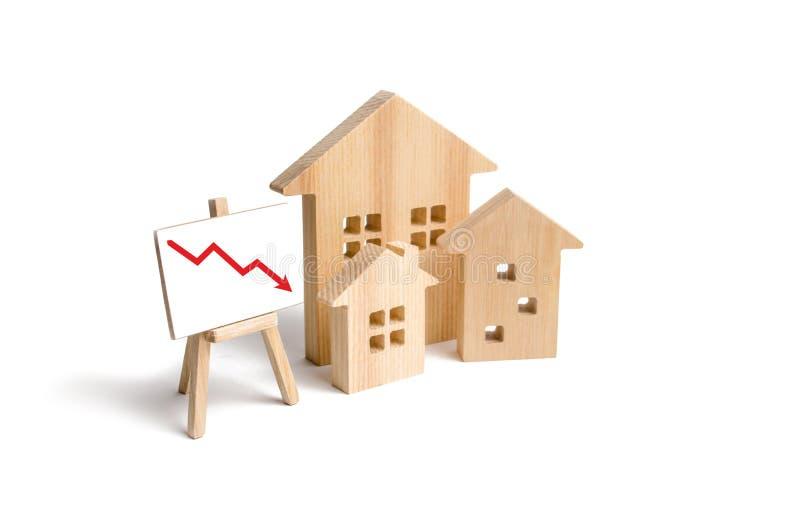 Zahlen Holzhäuser und roter Pfeil unten Das Konzept von fallenden Preisen und von Nachfrage nach Immobilien, Krise und Rezession lizenzfreie stockfotografie