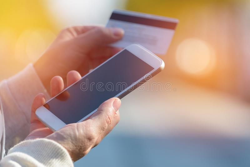 Zahlen mit dem Smartphone und Kreditkarte im Freien stockfotografie