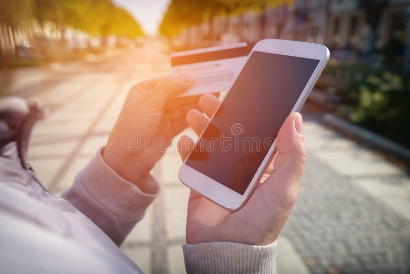 Zahlen mit dem Smartphone und Kreditkarte im Freien lizenzfreies stockfoto