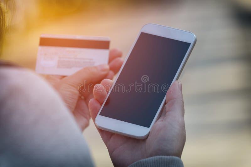 Zahlen mit dem Smartphone und Kreditkarte im Freien lizenzfreie stockfotografie