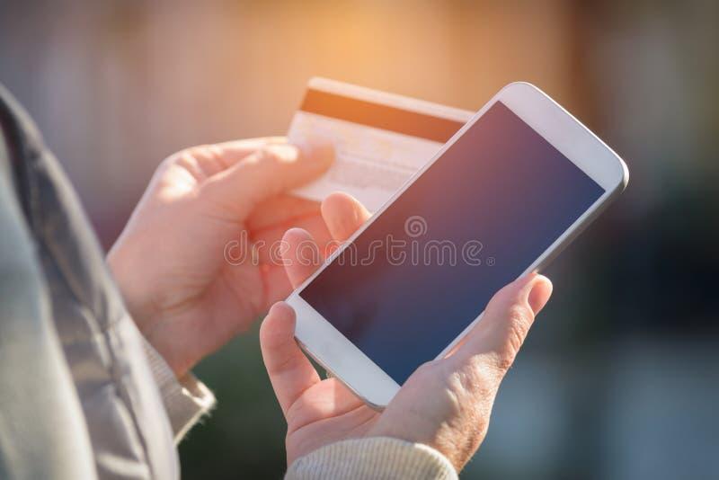 Zahlen mit dem Smartphone und Kreditkarte im Freien lizenzfreies stockbild