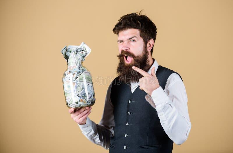 Zahlen von Zinsen auf Spareinlage Geschäftsmann, der seine Geldeinsparung zeigt Bärtiger Mann, der auf Glasgefäß mit Geld zeigt stockbilder