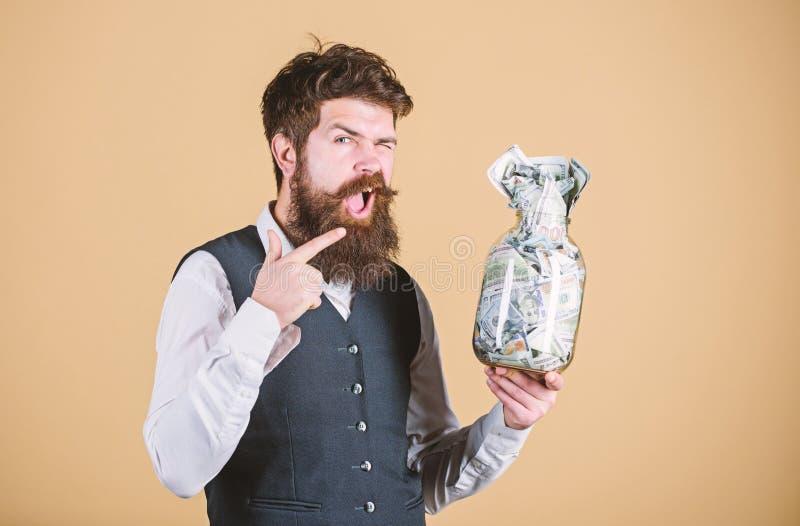 Zahlen von Zinsen auf Spareinlage Gesch?ftsmann, der seine Geldeinsparung zeigt B?rtiger Mann, der auf Glasgef?? mit Geld zeigt lizenzfreie stockfotos