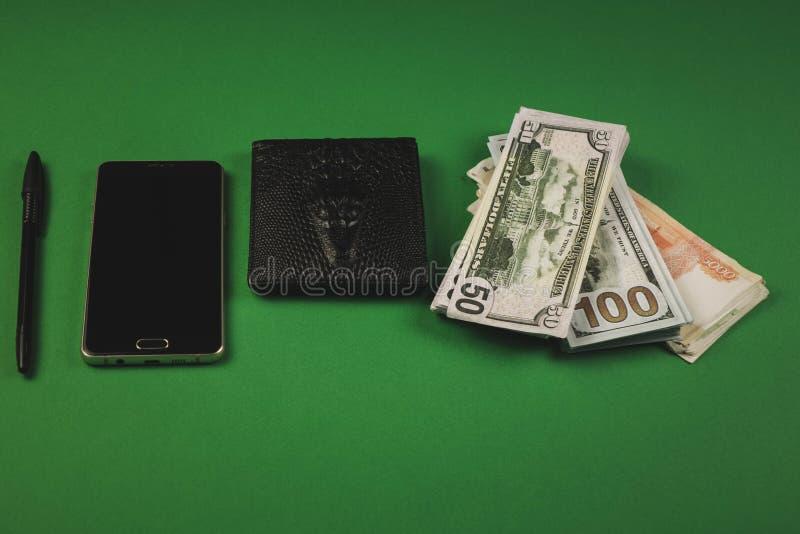 Zahlreiche Bargeld-Packs, Telefon, schwarzer Stift und Geldbeutel auf grünem Hintergrund stockfotografie
