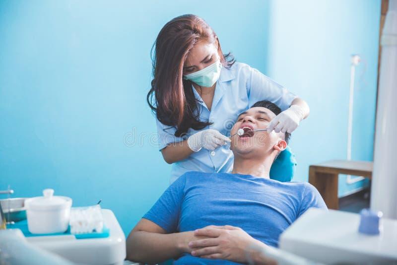 Zahnärzte, die an jungem männlichem Patienten überprüfen und arbeiten stockfotografie