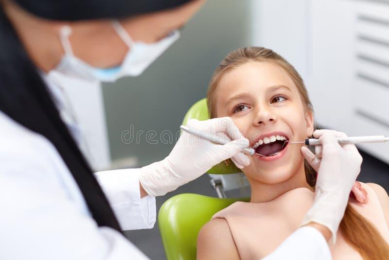 Zahnüberprüfung im Büro des Zahnarztes Untersuchungsmädchenzähne des Zahnarztes lizenzfreies stockbild
