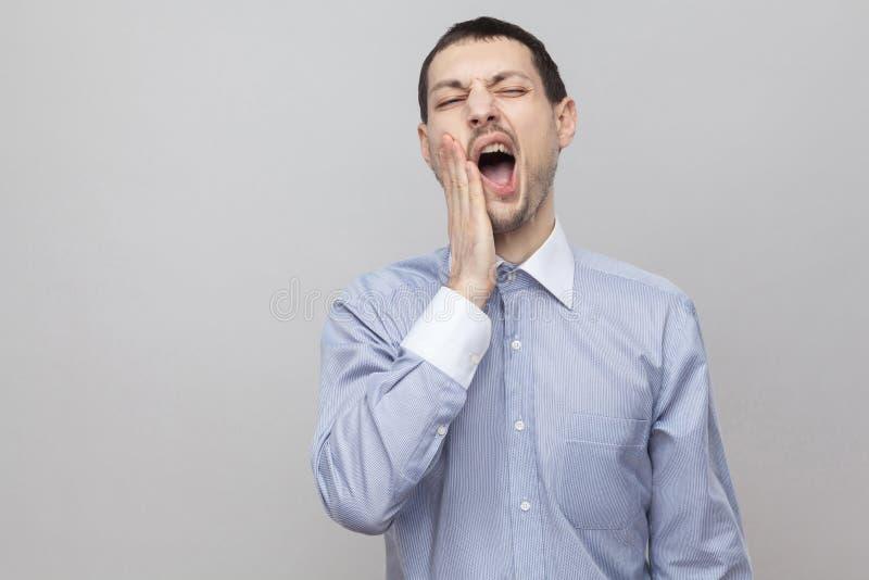 Zahn-Schmerz Porträt des hübschen Borstengeschäftsmannes in der klassischen hellblauen Hemdstellung mit offenem Mund und dem glau stockfoto