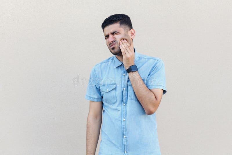 Zahn-Schmerz Portr?t des traurigen h?bschen jungen b?rtigen Mannes der Sorge in der blauen Hemdstellung, seine Backe ber?hrend, w stockfoto