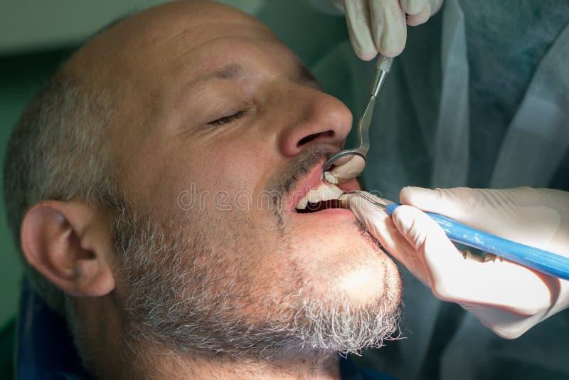 Zahnarzt überprüft die Zähne eines Mannes auf allgemeinem Mund-hygene stockbilder