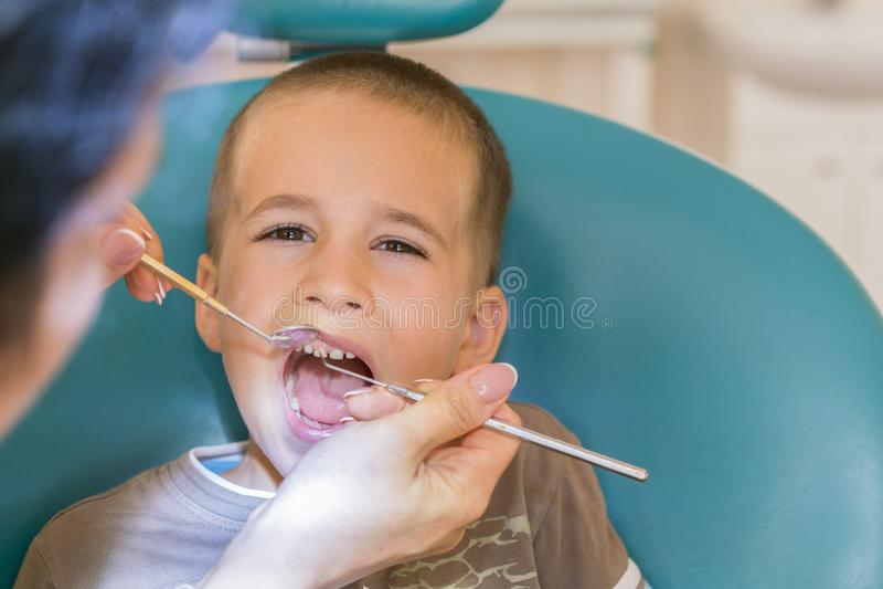 Zahnarzt behandelt ein boy& x27; s-Zähne Children& x27; s-Zahnheilkunde, pädiatrische Zahnheilkunde Ein weibliches stomatologist  lizenzfreie stockfotografie