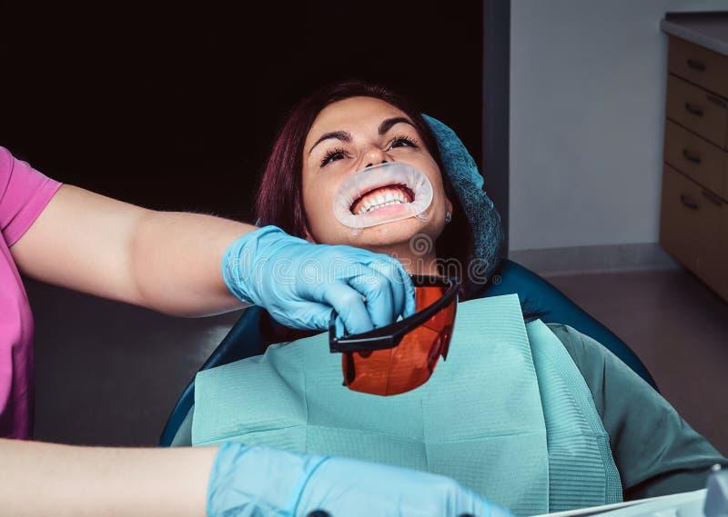 Zahnarzt behandelt weiblichen Patienten, der in einem zahnmedizinischen Stuhl in der Klinik sitzt lizenzfreie stockbilder