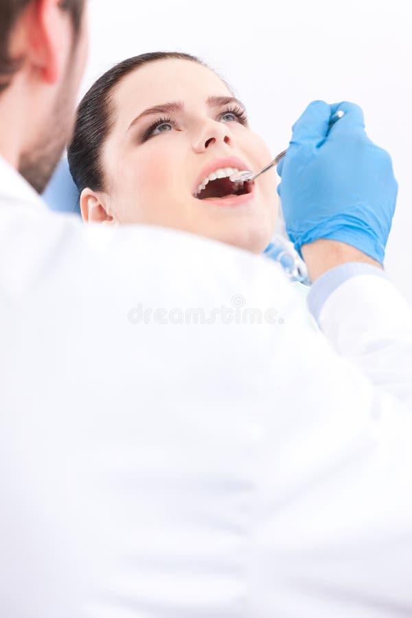 Zahnarzt in den medizinischen Handschuhen überprüft die Mundhöhle lizenzfreie stockfotos