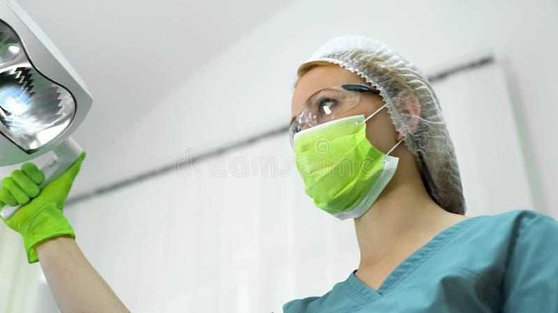 Zahnarzt in den Schutzmaskengläsern und Kappenvorbereitung vor mündlicher Prüfung stockfotografie