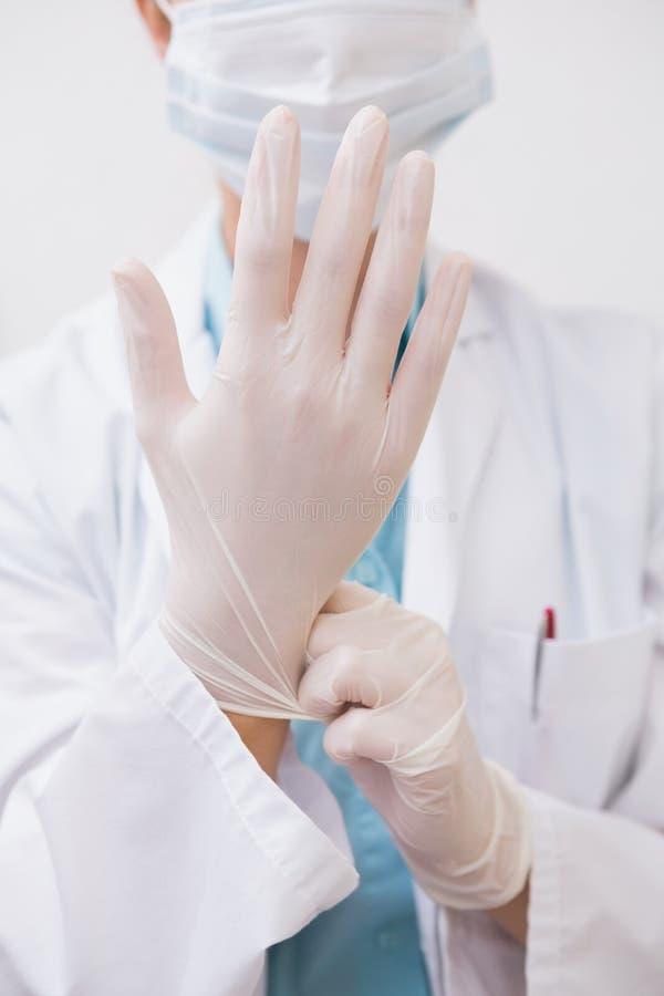 Zahnarzt, der auf chirurgische Handschuhe zieht lizenzfreies stockfoto