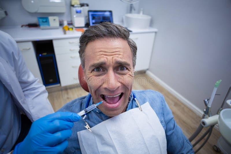 Zahnarzt, der Betäubungsmittel in erschrockenem männlichem geduldigem Mund einspritzt stockbild