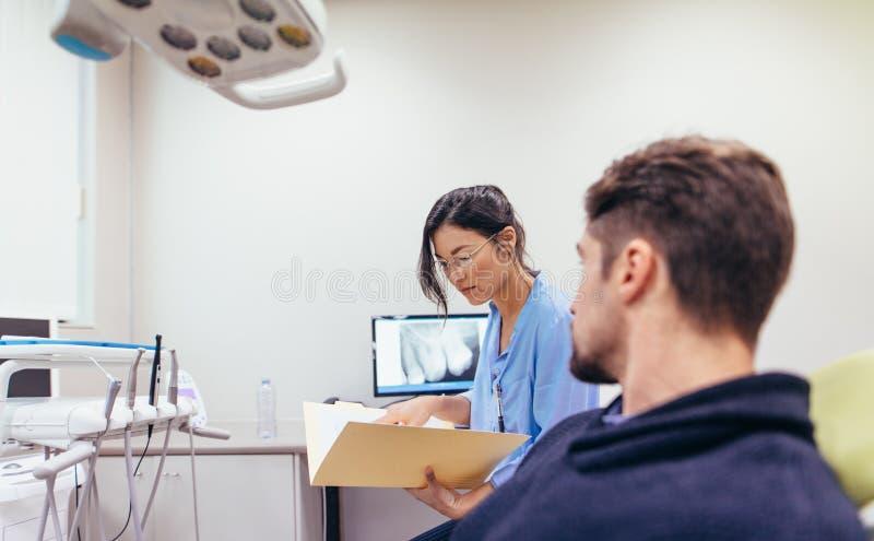 Zahnarzt, der die Berichte des Patienten in der Klinik überprüft stockfotos