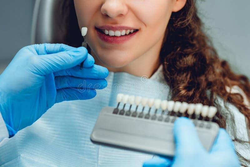 Zahnarzt, der Farbe von junge Frau ` s Z?hnen ?berpr?ft und vorw?hlt Weicher Fokus lizenzfreie stockfotos