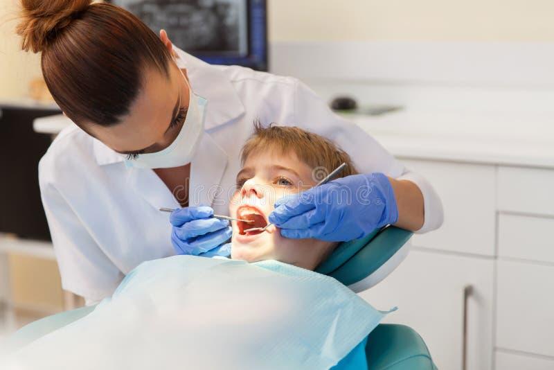 Zahnarzt, der geduldige Zähne überprüft lizenzfreie stockfotografie