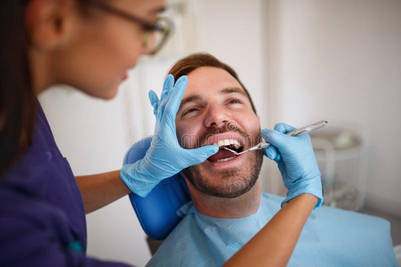 Zahnarzt, der herauf patient's Zähne mit zahnmedizinischem Spiegel überprüft stockfotos