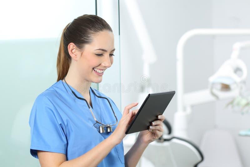 Zahnarzt, der on-line-Informationen in einer Tablette konsultiert lizenzfreies stockfoto