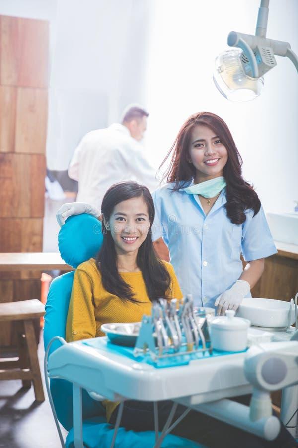 Zahnarzt, der mit weiblichem Patienten in der zahnmedizinischen Klinik lächelt lizenzfreie stockfotografie