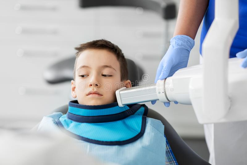 Zahnarzt, der Röntgenstrahl von den Kinderzähnen an der zahnmedizinischen Klinik macht lizenzfreies stockfoto