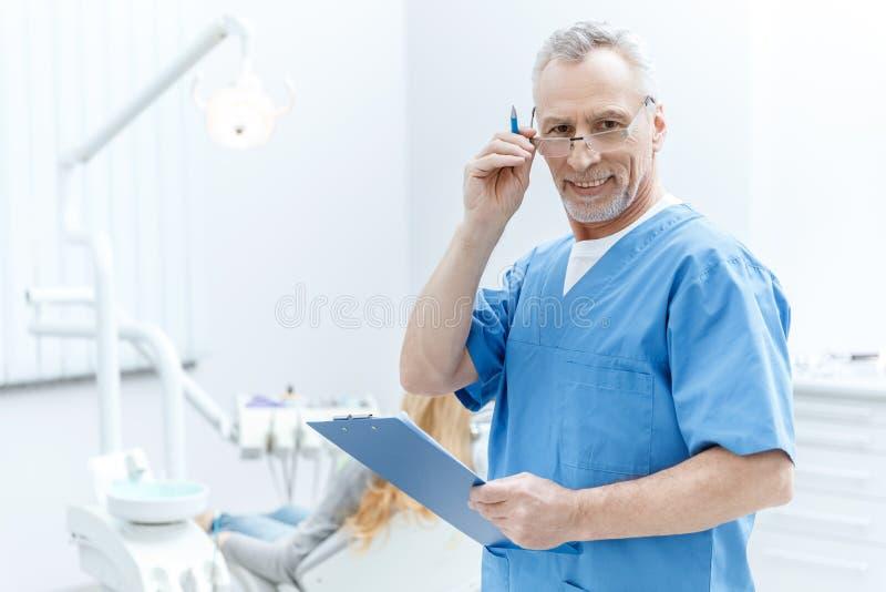 Zahnarzt in der Uniform mit Klemmbrett in der zahnmedizinischen Klinik mit Patienten hinten stockfoto