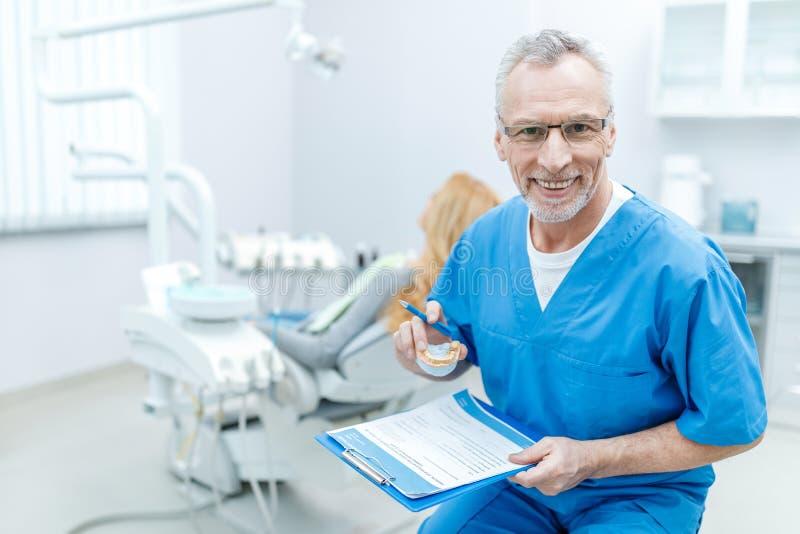 Zahnarzt in der Uniform mit Klemmbrett in der zahnmedizinischen Klinik mit Patienten hinten stockfotos