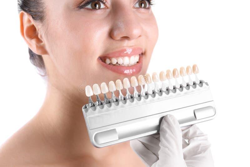 Zahnarzt, der Zahnfarbe der jungen Frau auf weißem Hintergrund überprüft stockfotografie