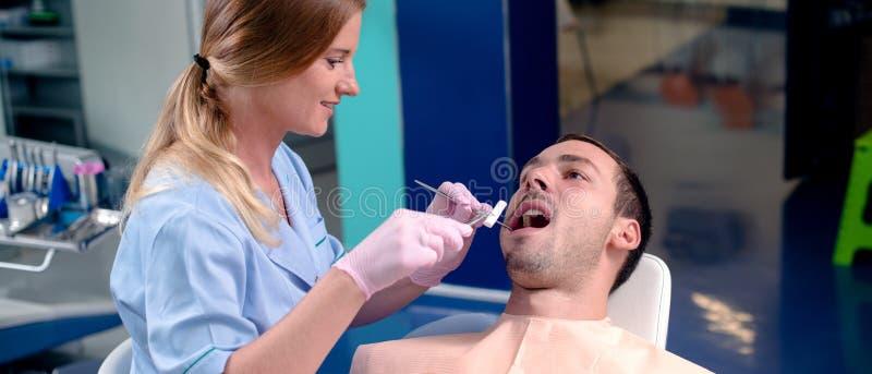 Zahnarzt, der zahnmedizinische Ausrüstung auf Mannzähnen verwendet stockfotos