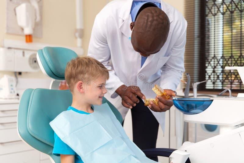 Zahnarzt, der zahnmedizinisches Verfahren erklärt stockfoto