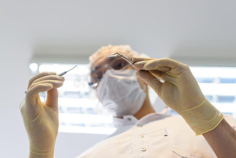 Zahnarzt des jungen Mannes in den Schutzhandschuhen und in einer Maske lizenzfreies stockfoto