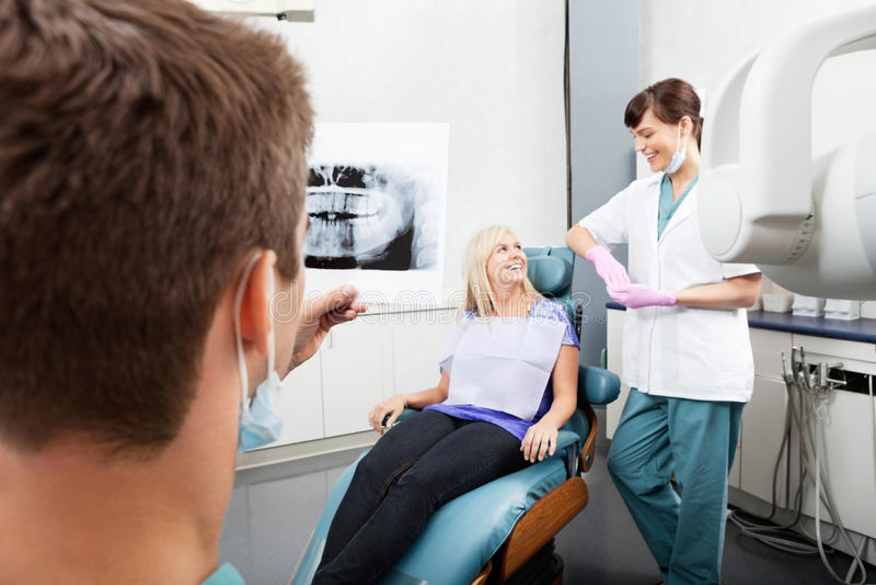 Zahnarzt-Examining-Röntgenbild mit Frau lizenzfreies stockbild