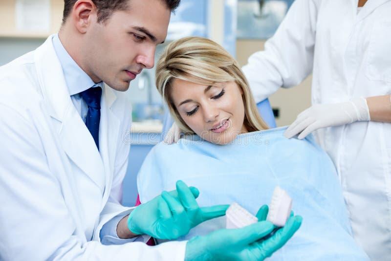 Zahnarzt mit geduldiger und zahnmedizinischer Form stockbild