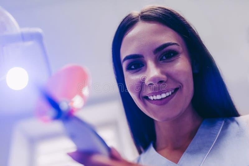 Zahnarzt mit UVlampe in der Klinik lizenzfreie stockfotos