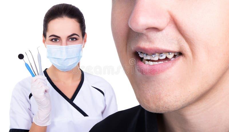 Zahnarzt oder Orthodontist und junger Mann mit Klammern auf Zähne isola lizenzfreies stockbild