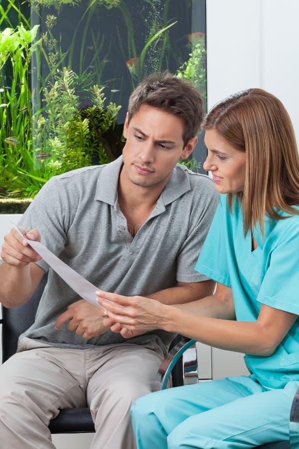 Zahnarzt-And Patient Reading-Bericht stockfoto