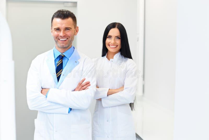 Zahnarzt Team an der zahnmedizinischen Klinik Zwei lächelnde Doktoren bei ihrer Arbeit stockbild