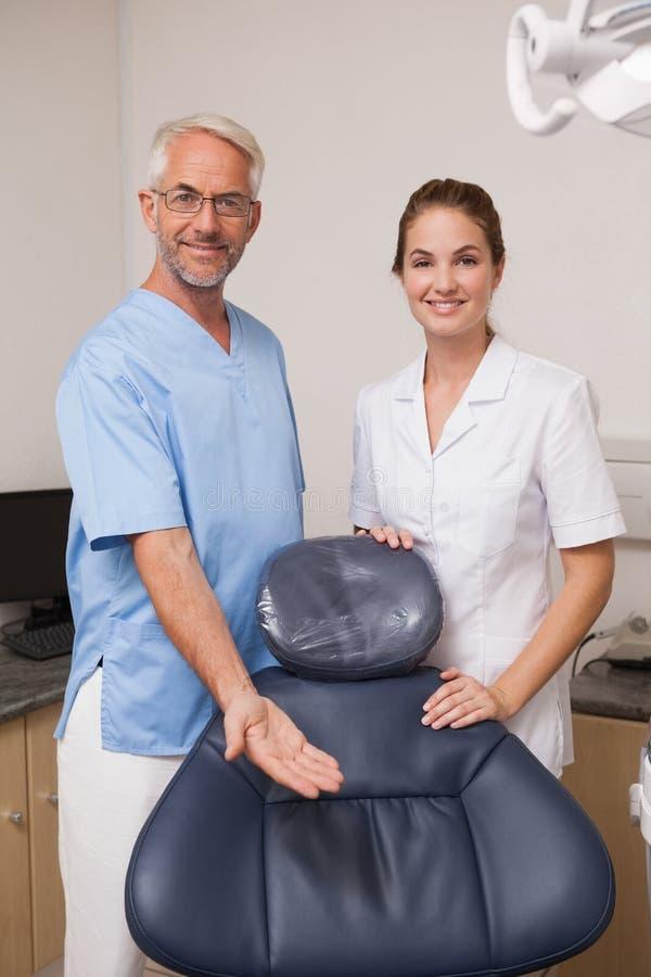 Zahnarzt und Assistent, die an der Kamera einlädt Sie zum Stuhl lächelt lizenzfreie stockfotografie