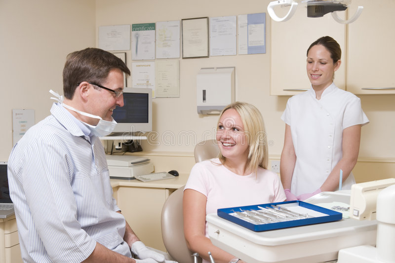 Zahnarzt und Assistent im Prüfungraum mit Frau stockfoto
