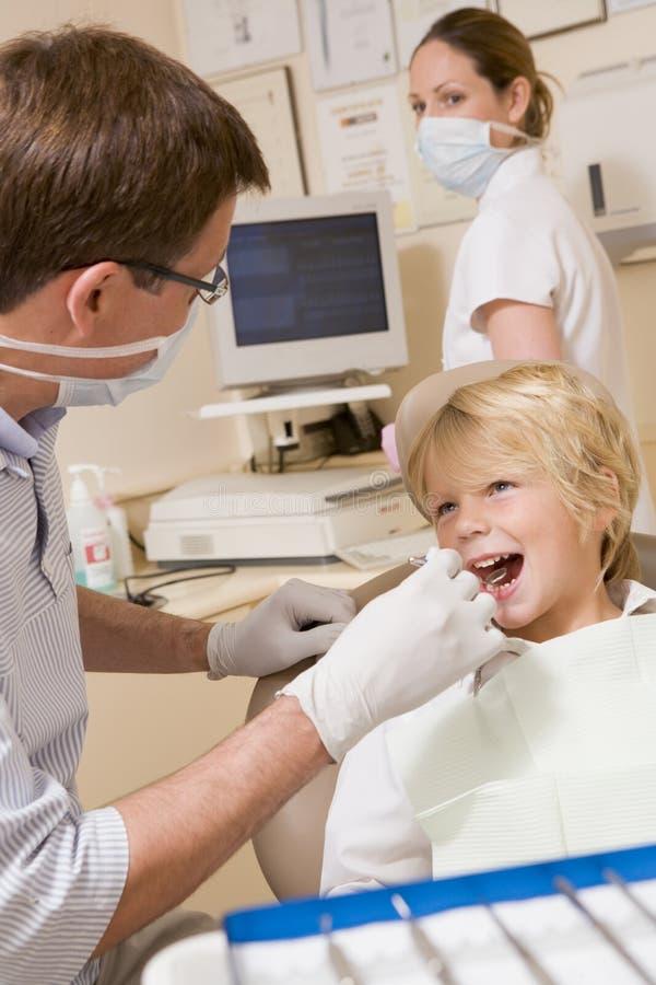 Zahnarzt und Assistent mit jungem Jungen lizenzfreies stockbild
