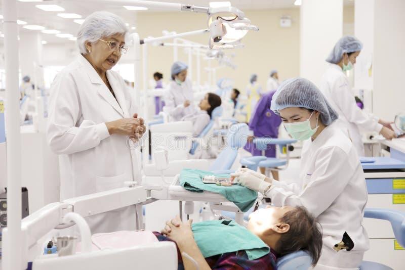 Zahnarzt und ihr Lehrer, die an arbeiten und alter Patient stockfoto