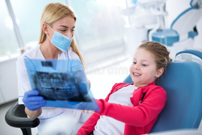 Zahnarzt und kleines Mädchen, die Röntgenstrahl von Zähnen betrachten lizenzfreie stockfotos